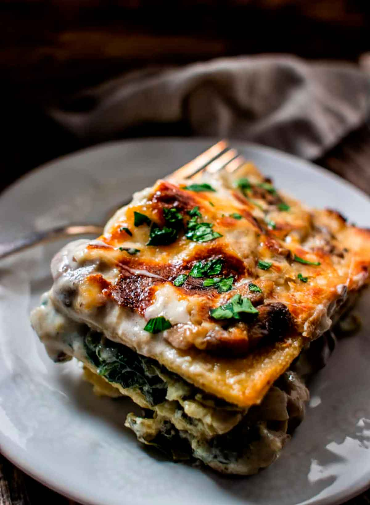 A slice of mushroom, spinach and artichoke lasagna on a plate.