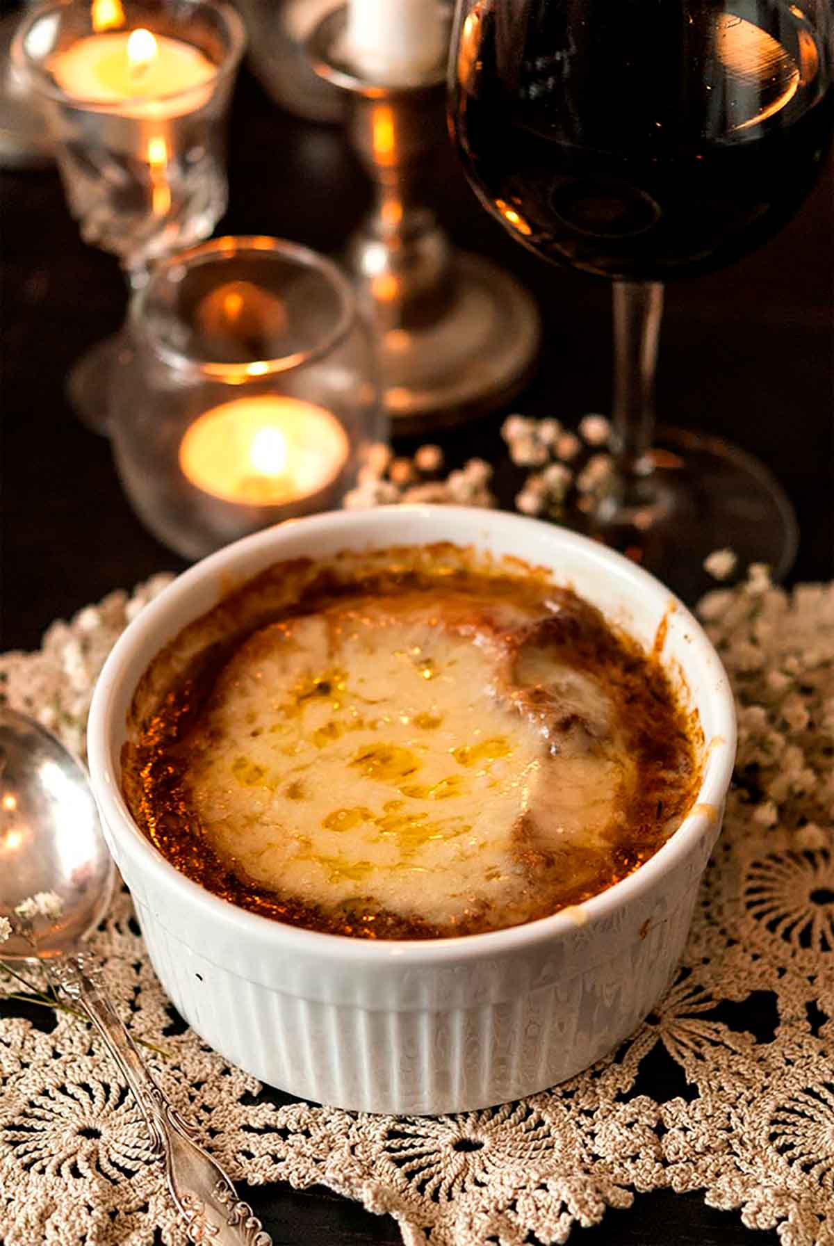 A bowl of French onion soup on a small lace doily in front of a candle, candle stick and glass of red wine.