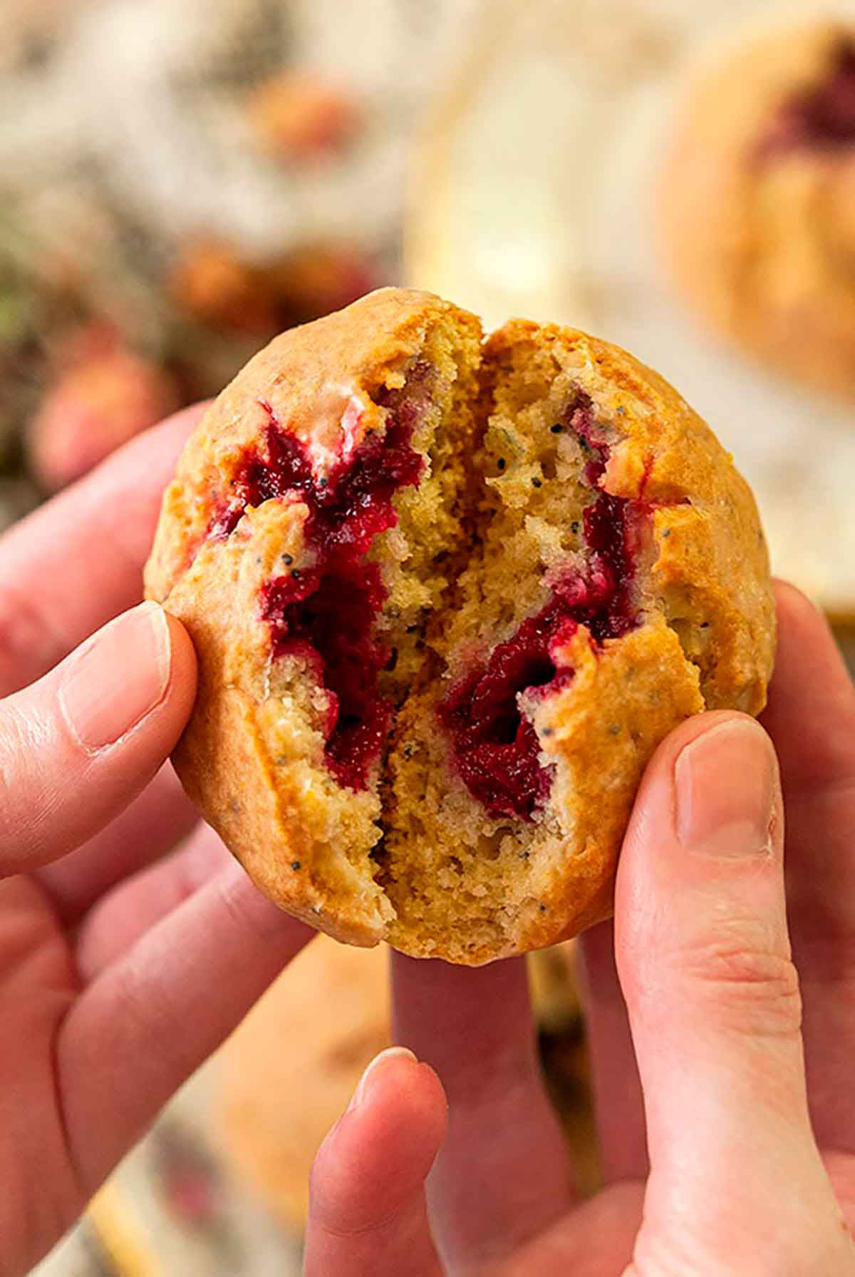 Hands opening up a scone showing raspberries inside.
