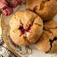 Glazed raspberry lemon poppyseed scones on a plate beside dry roses.