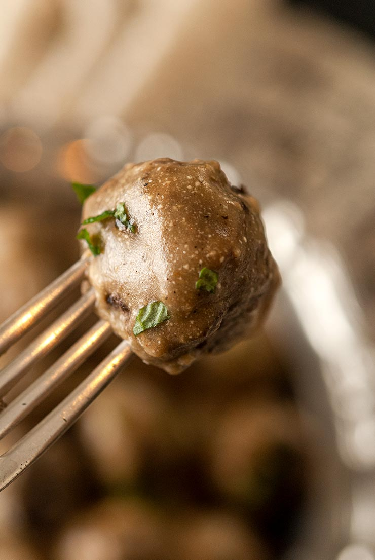 A closeup of one Swedish meatball on a fork..
