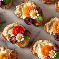 Beautifully garnished crostini on a marble plate.