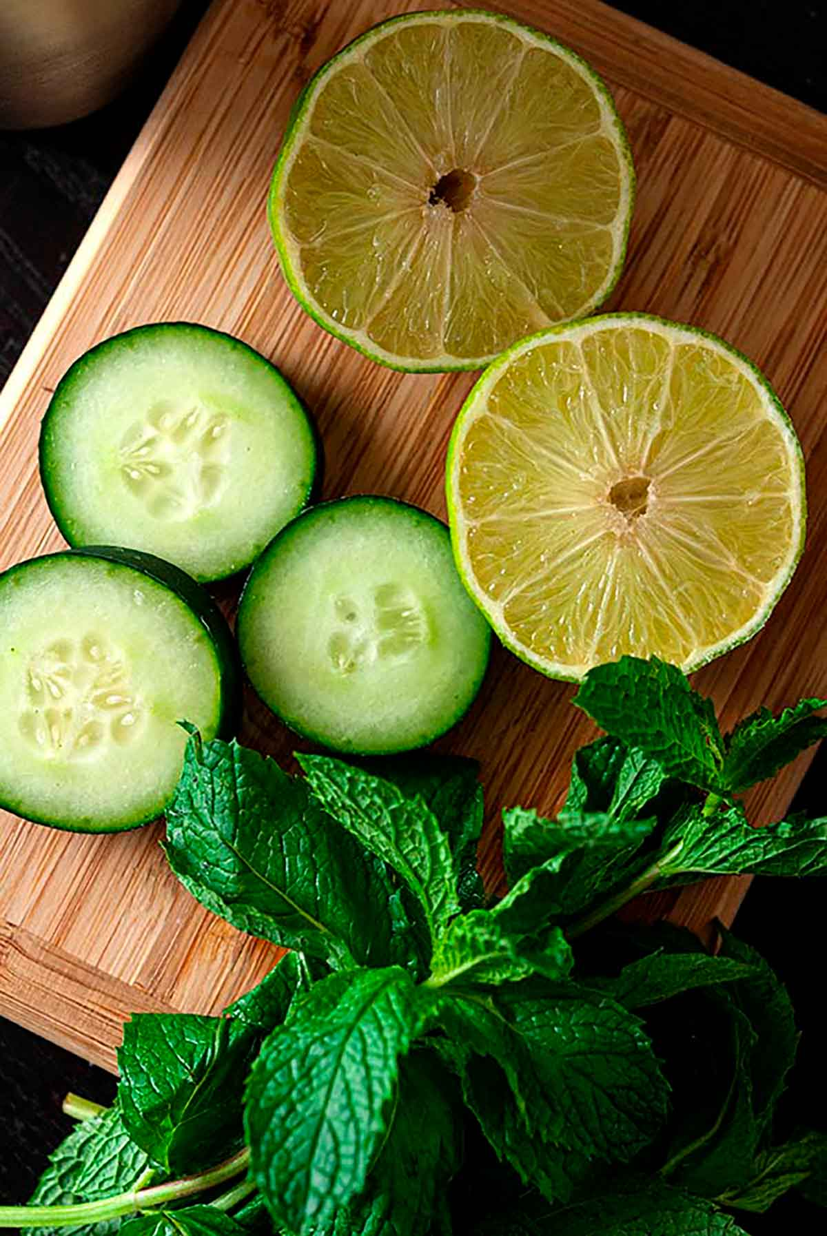 A small cutting board with 3 cucumber slices, 2 lime slices and a sprig of fresh mint.