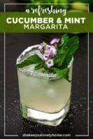 A cucumber mint margarita, garnished with small flowers and mint, on a table lightly sprinkled with salt.