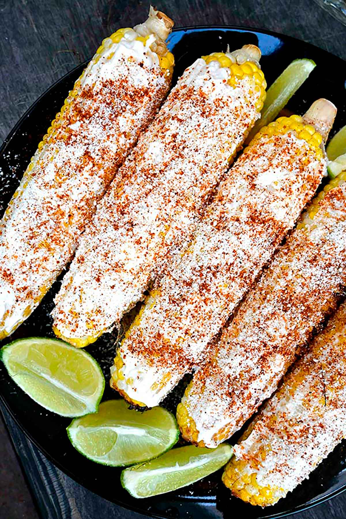 Elote (spiced and cheese-sprinkled corn) on a plate with 4 lime wedges.