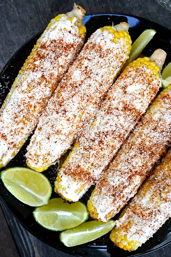Elote (mexican street corn) on a plate with 4 lime wedges.