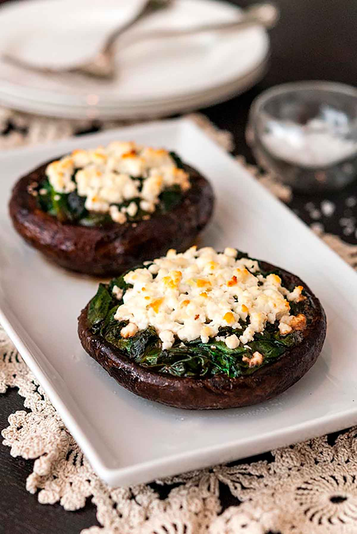 2 spinach and feta-stuffed mushroom caps on a plate on a table, lined with lace with 2 stacked plates in the background.