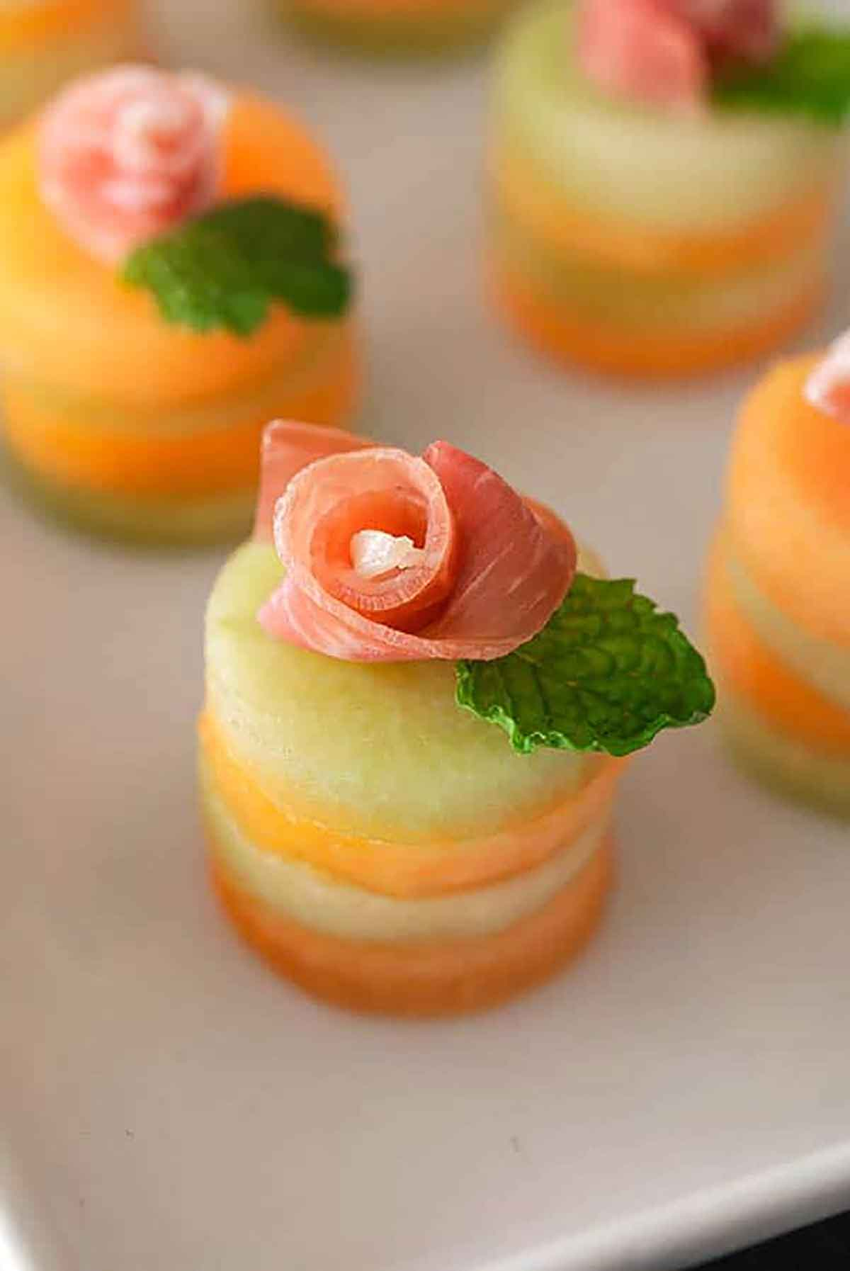 4 small melon appetizers with prosciutto roses and mint leaves on top.