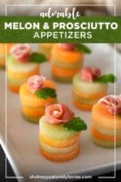 8 small melon appetizers with a prosciutto rose and mint leaves on top, in front of a lace tablecloth.