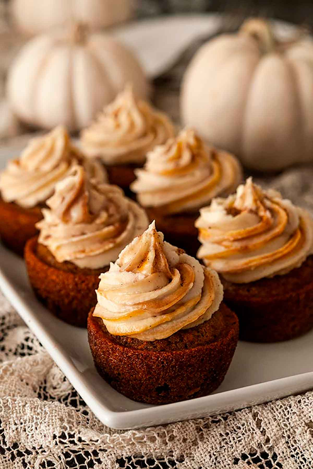 6 carrot cupcakes on a plate in front of white pumpkins.