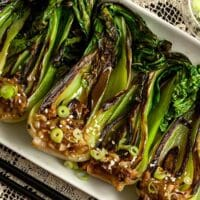 Seared baby bok choy on a plate, sitting on a table with a lace table cloth.