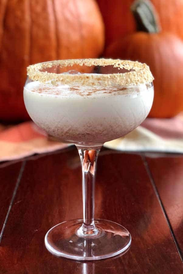 A cocktail garnished with crumbs on a wooden table, in front of pumpkins.