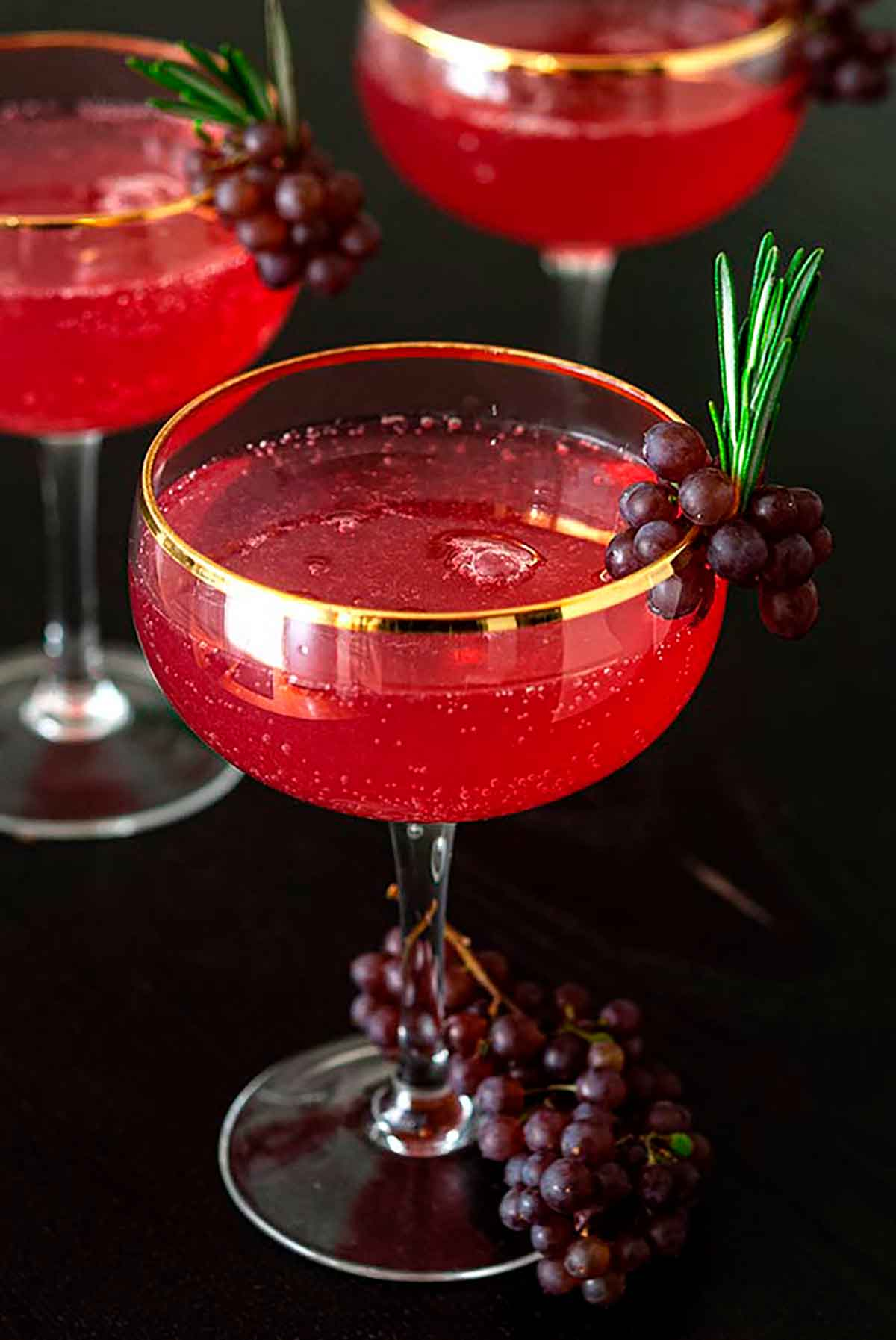 3 cocktails garnished with small grapes and sprigs of rosemary.