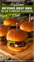 4 barbecue sliders on a wooden board on a lace tablecloth in front of bowls of garnishes.