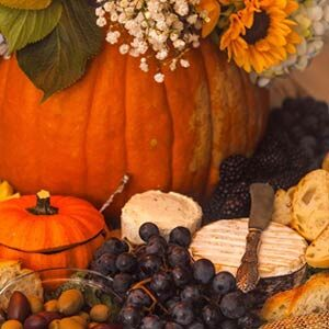 An array of cheeses, grapes, breads and olives beside a large pumpkin filled with flowers.