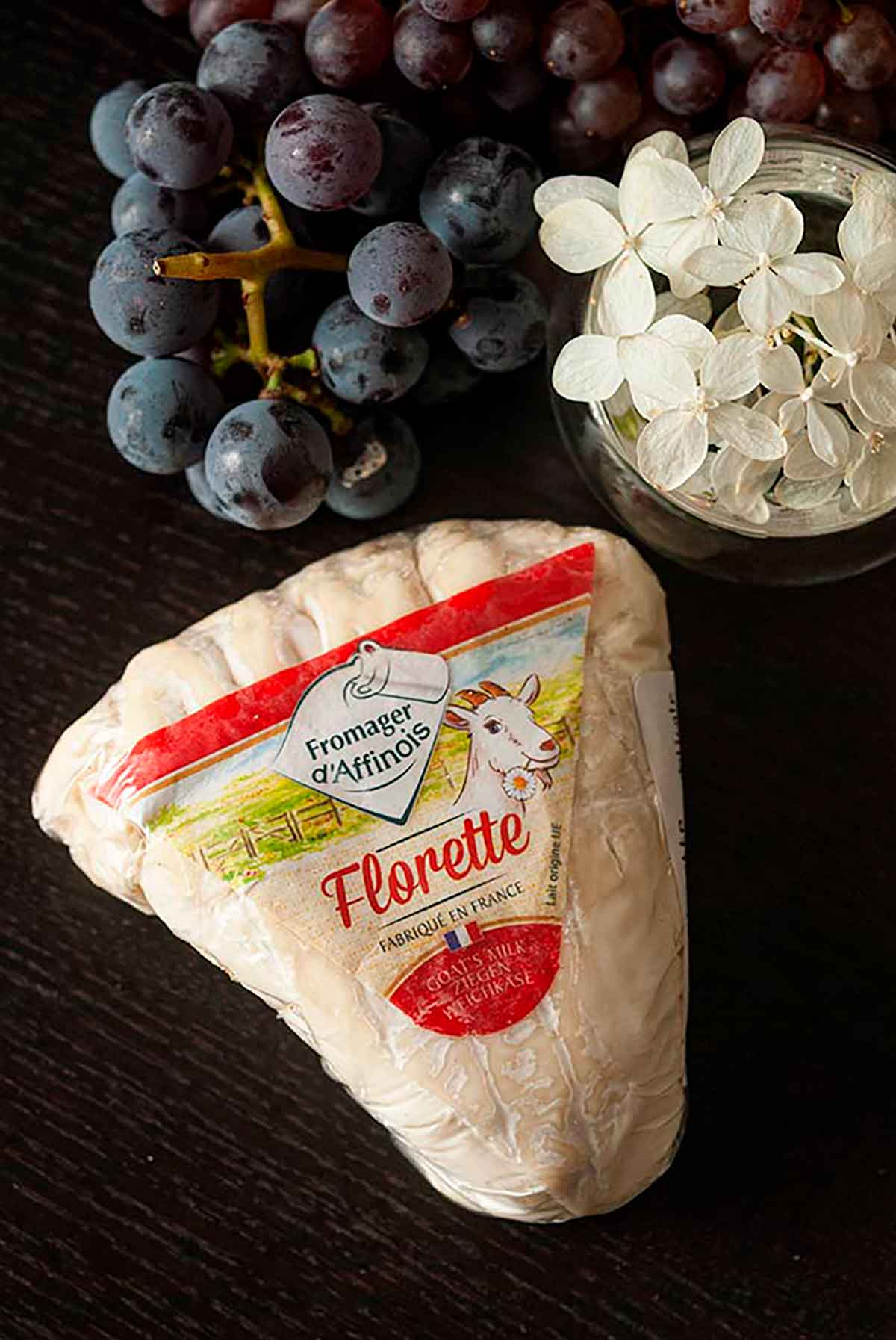 A package of Florette cheese on a table beside a small bunch of grapes and a small bowl of flowers.