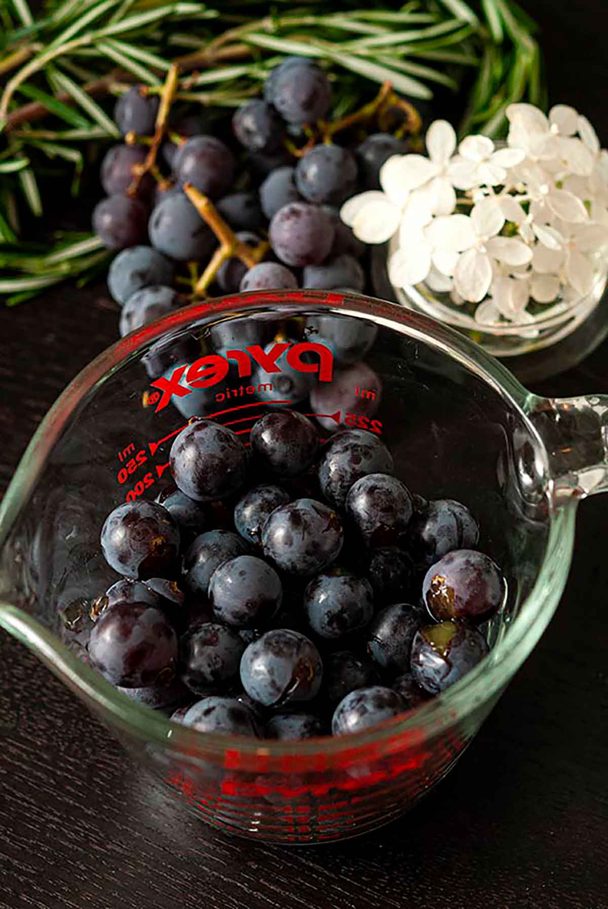 A measuring cup full of grapes beside a small bowl of flowers on a table.