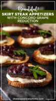6 steak appetizers on a marble slate, garnished with tiny grapes, arugula and dripping cheese.