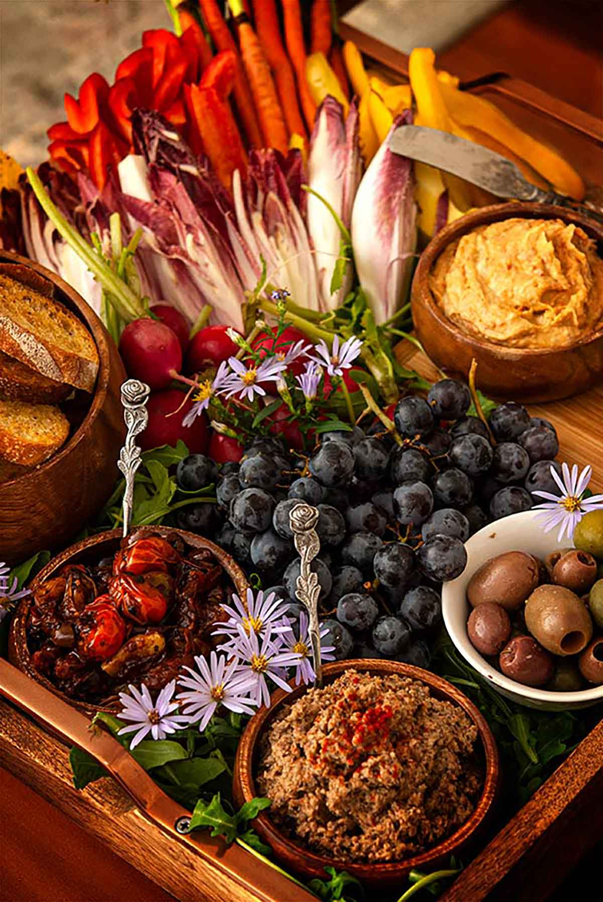 A crudités platter with vegetables, dips, olives, grapes and a bowl of bread on a tray.