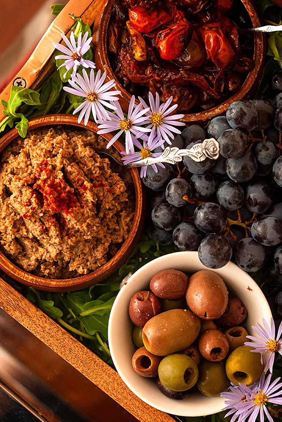 Bowls of bruschetta, pate and olives surrounded by grapes, arugula and flowers in a tray.
