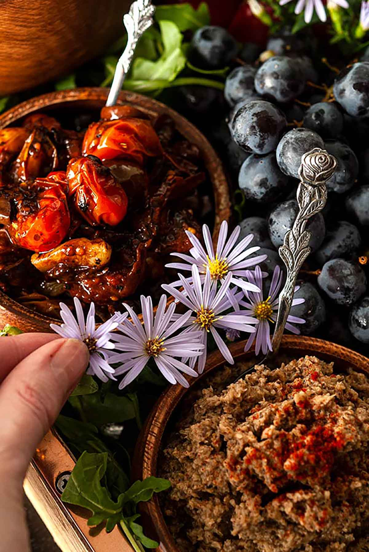 Fingers adding flowers between bowls of dips, surrounded by grapes and arugula in a tray.