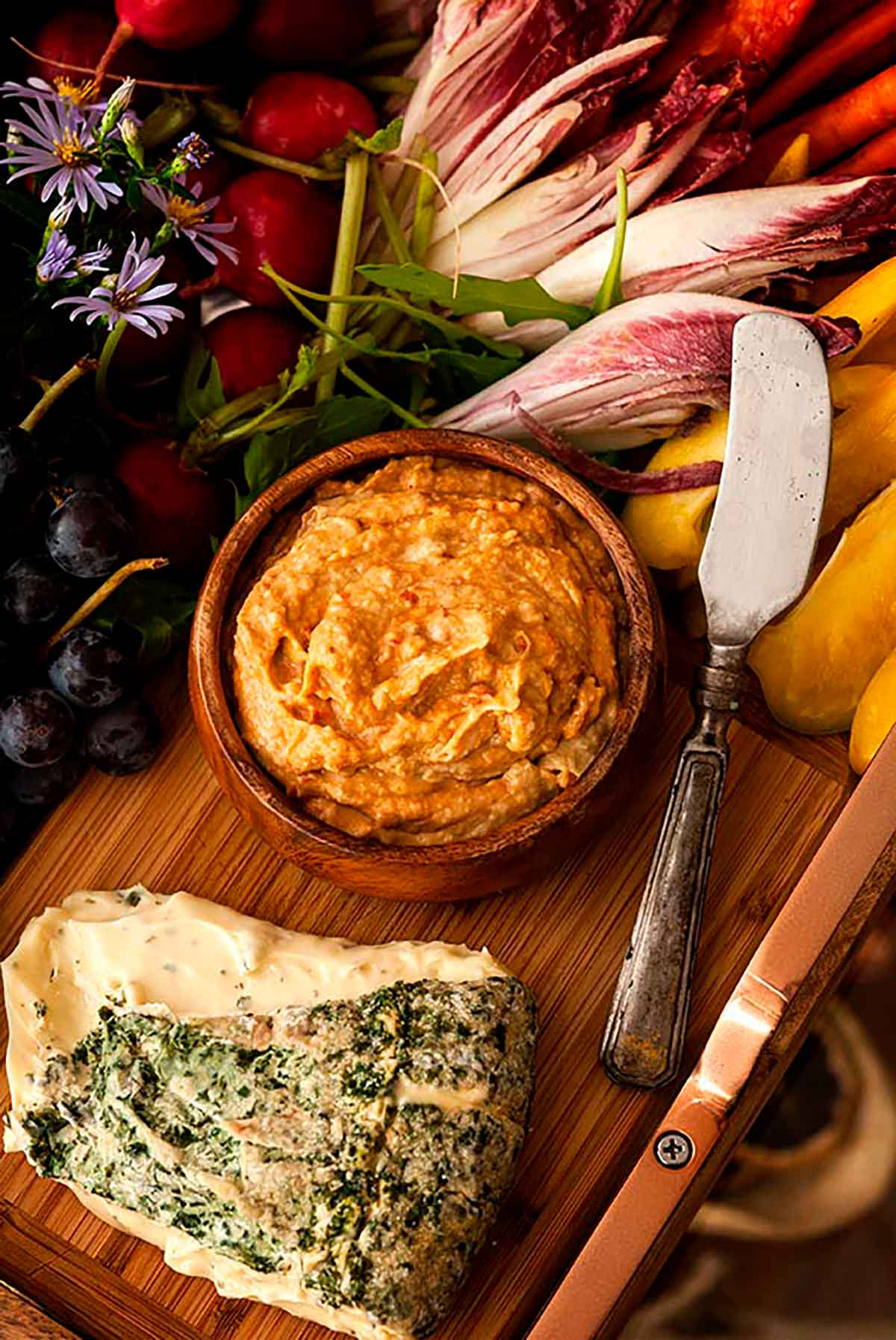 A bowl of hummus on a board with herbed cheese and a cheese knife, surrounded by vegetables.
