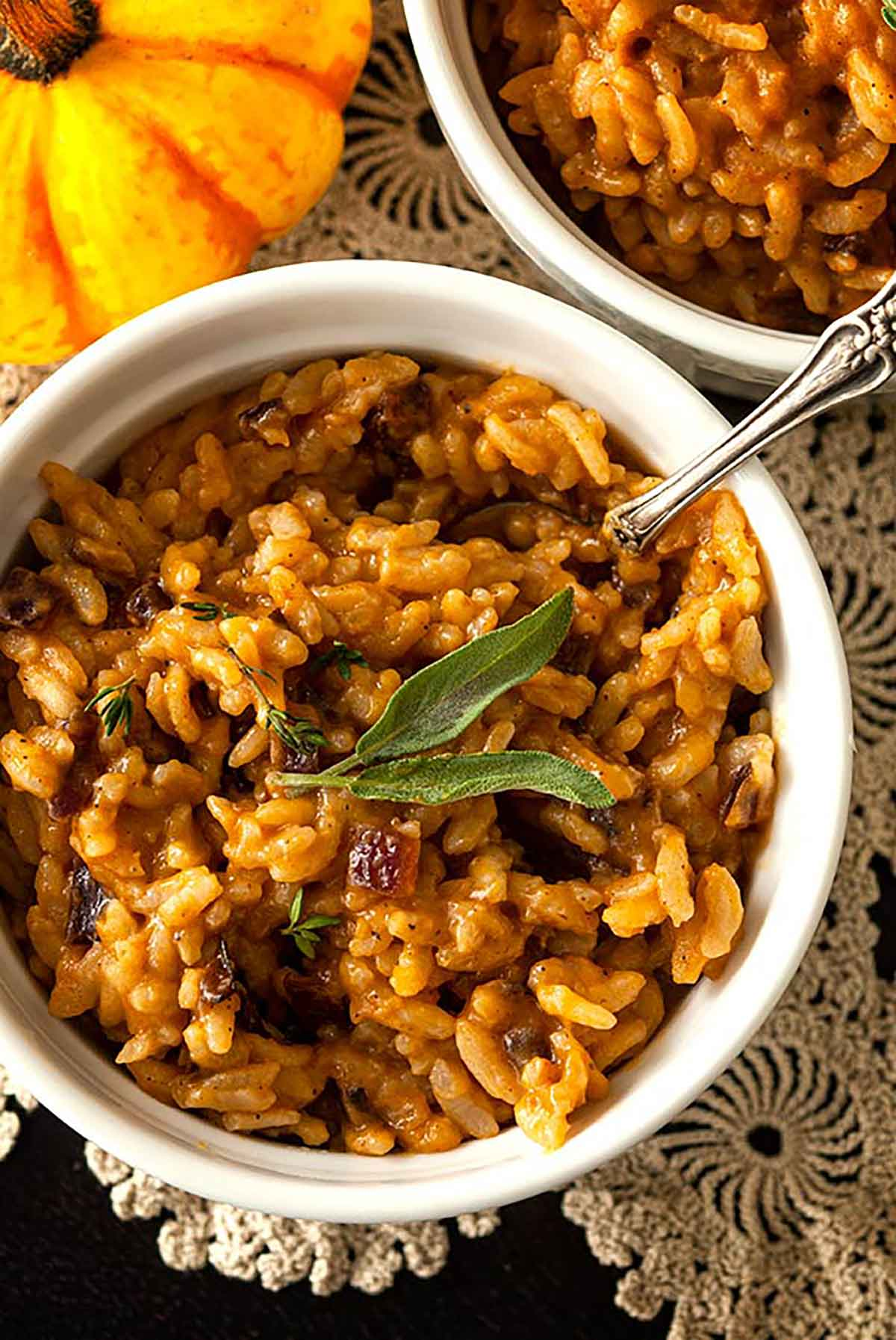 A bowl of pumpkin risotto, garnished with 2 sage leaves, on a lace table cloth beside another bowl and small pumpkin.