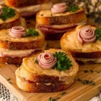 6 mini croque monsieur with a small ham rose garnishes and parsley on a wooden cutting board, surrounded by flowers.