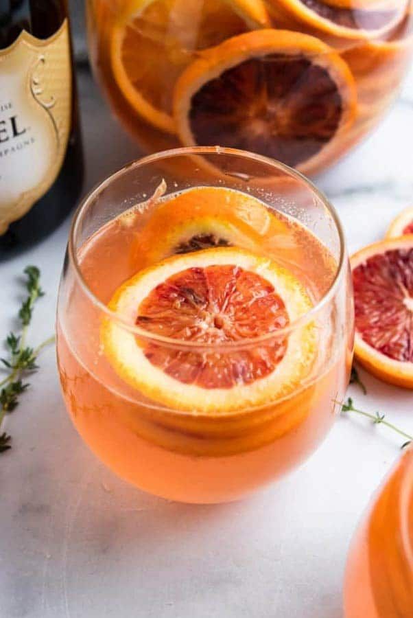 A blood orange champagne cocktail, garnished with an orange slice, beside a few stray orange slices on a table.