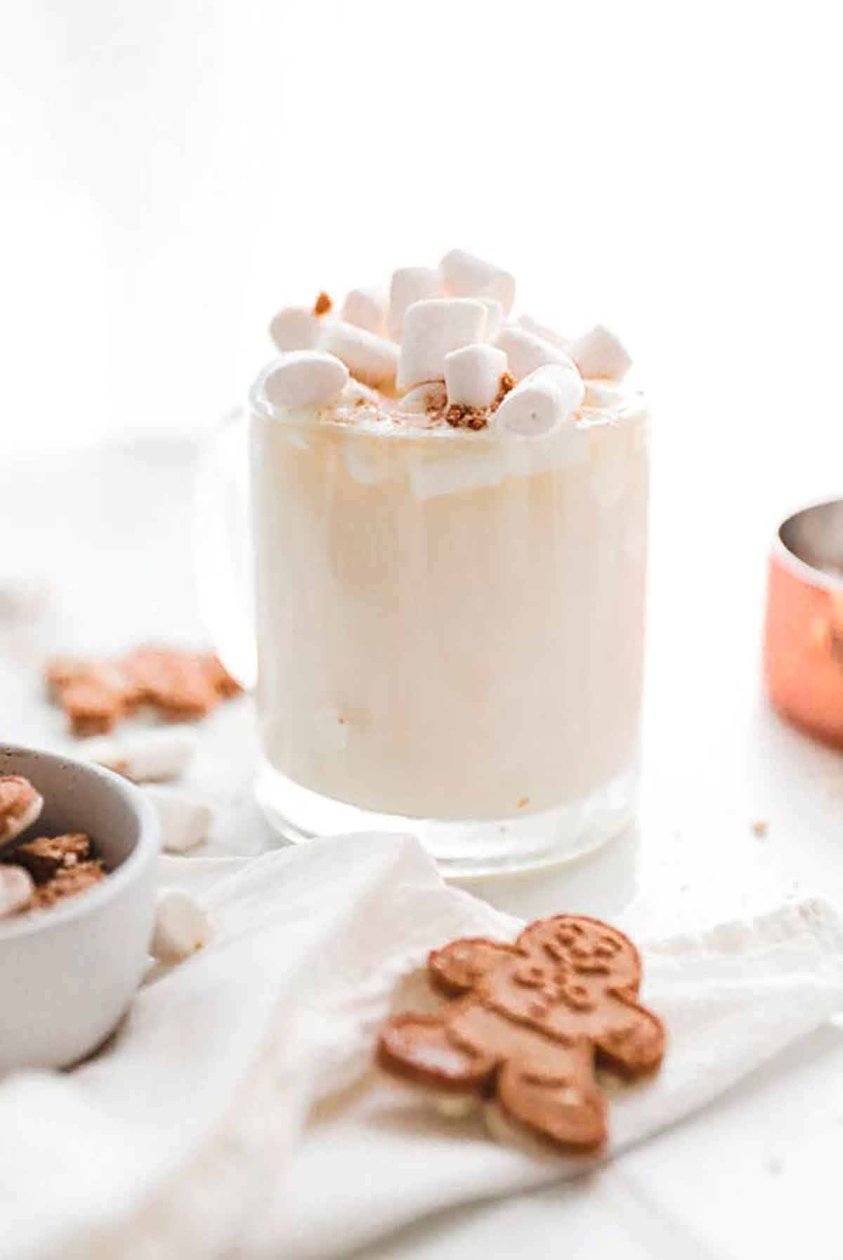 A creamy cocktail in a glass, topped with marshmallows and surrounded by cookies.
