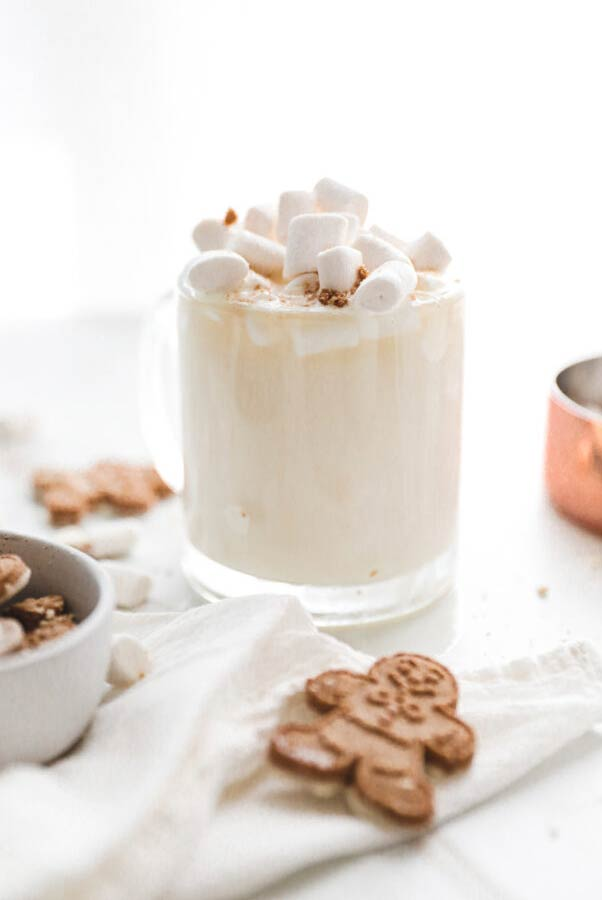 A white cocktail in a tumbler glass, full of marshmallows, on a table with gingerbread cookies.