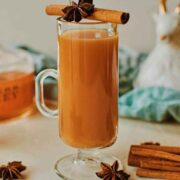 A cocktail in a mug, garnished with cinnamon, anise, and surrounded by cinnamon sticks and anise on a table.