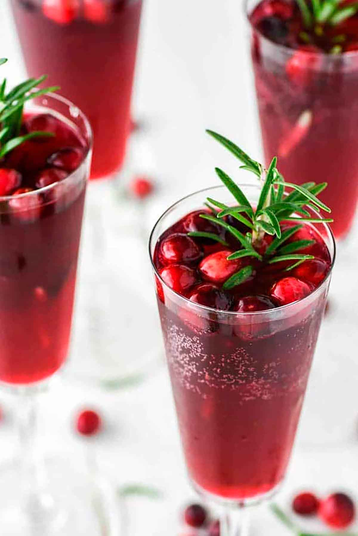 4 cranberry mimosas, garnished with cranberries and rosemary.