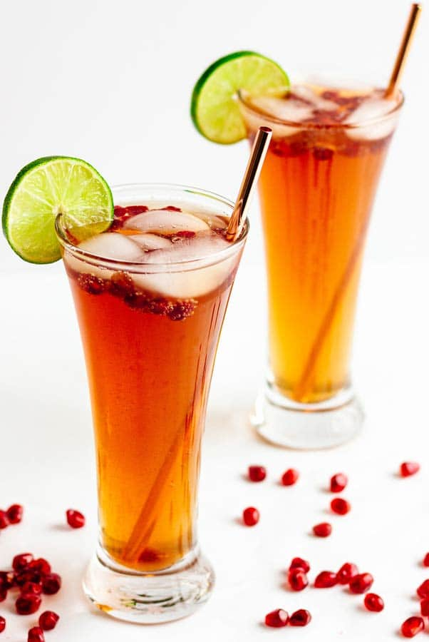 2 pomegranate lime spritzer cocktails, garnished with pomegranate seeds and lime slices.