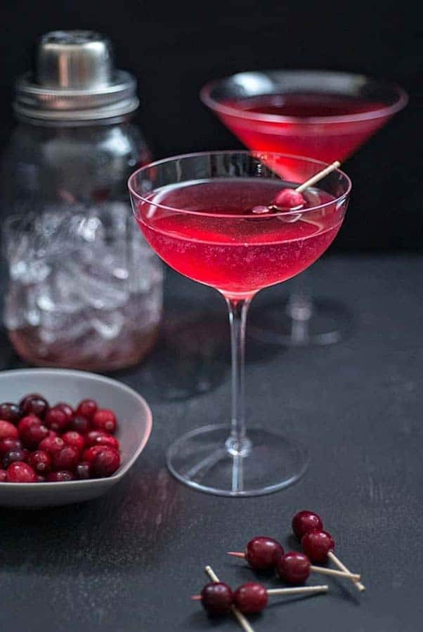 2 red cocktails in a dark setting, garnished with cranberries.