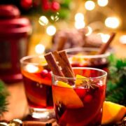 3 Gluhwein cocktails, garnished with cinnamon, orange and cranberries in a holiday setting.