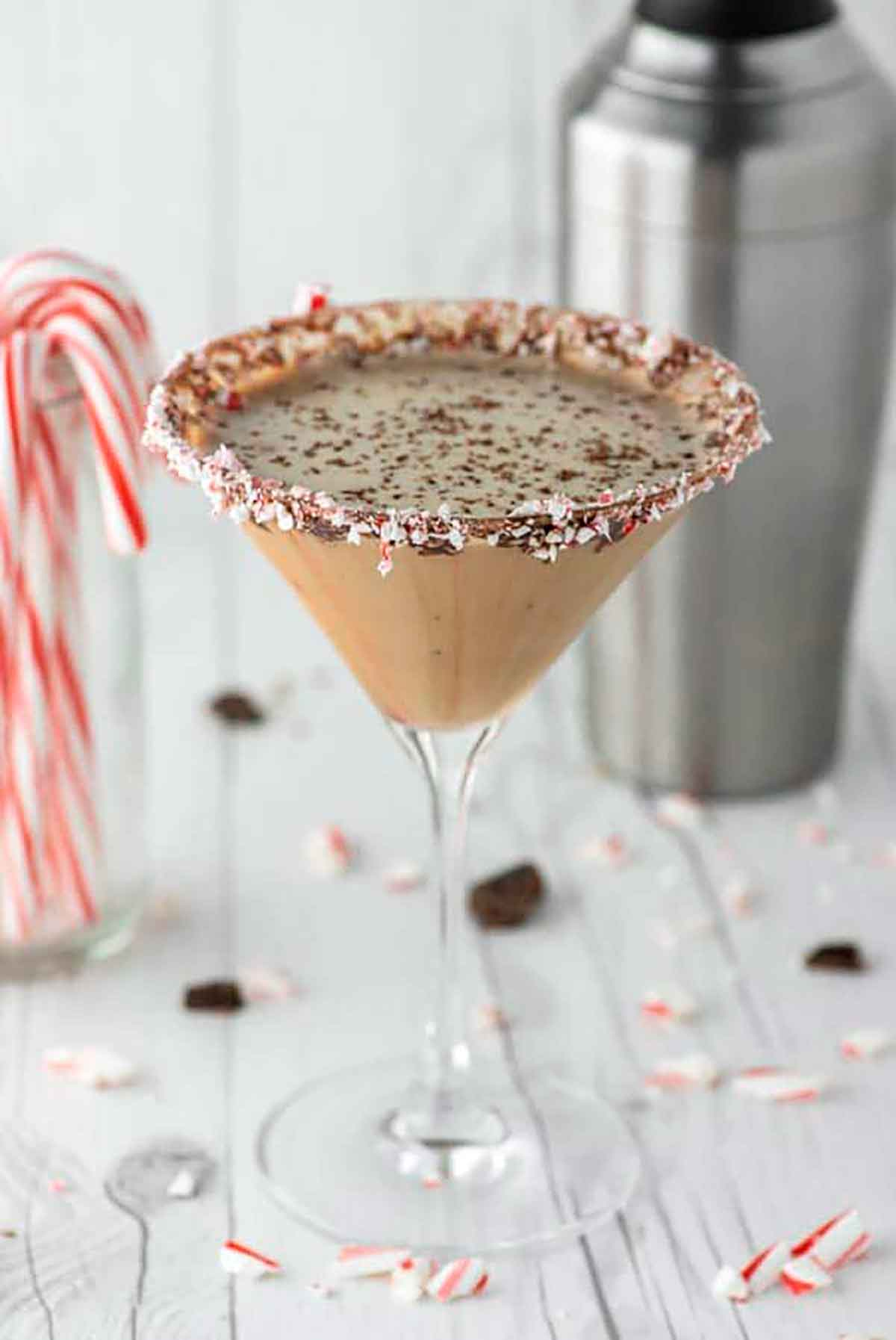 A creamy, chocolate cocktail beside a glass of candy canes and a cocktail shaker.