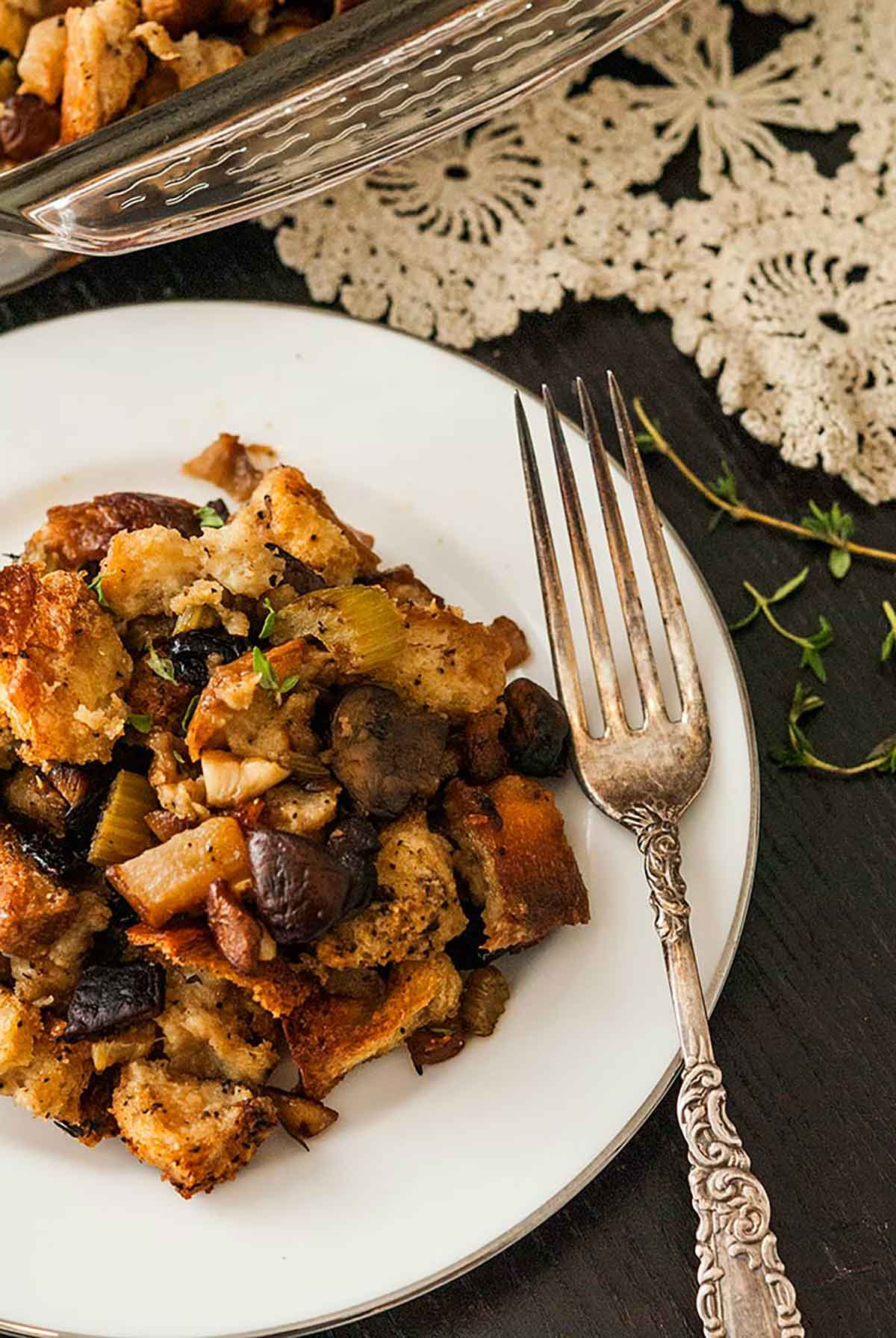 A plate of stuffing with a victorian-style fork on a black table with a lave table cloth and a few sprinkles of thyme.