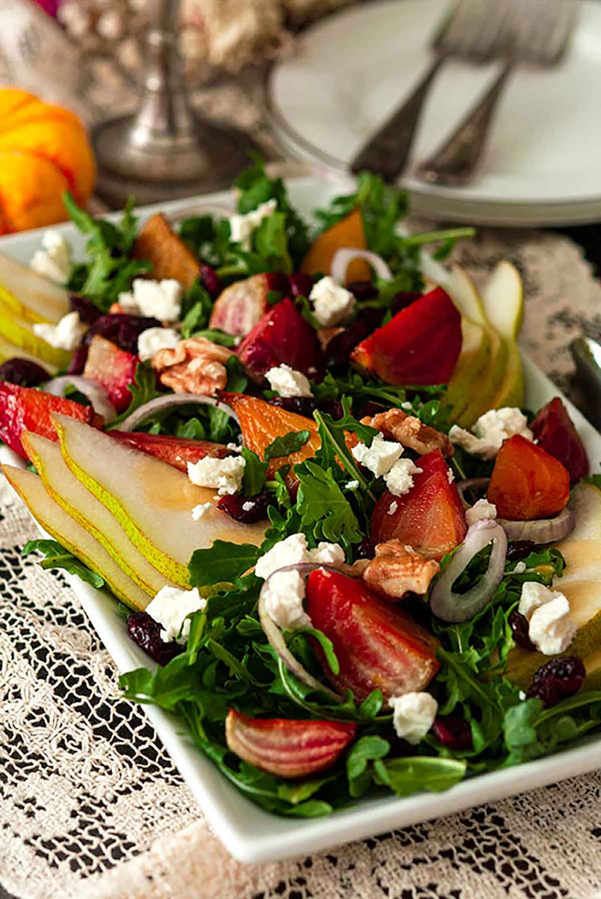 A salad with colorful vegetables, pears, berries and nuts on a lace table cloth with plates and forks in the background.