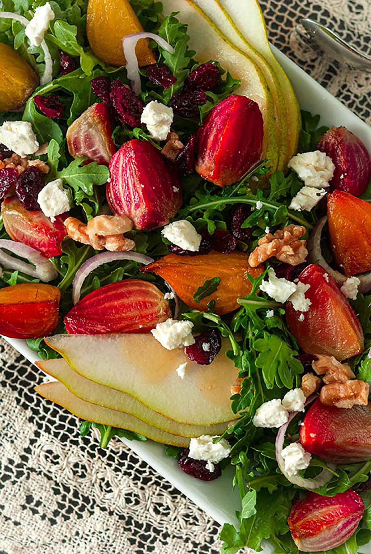 A salad with colorful vegetables, pears, berries and nuts on a lace table cloth.