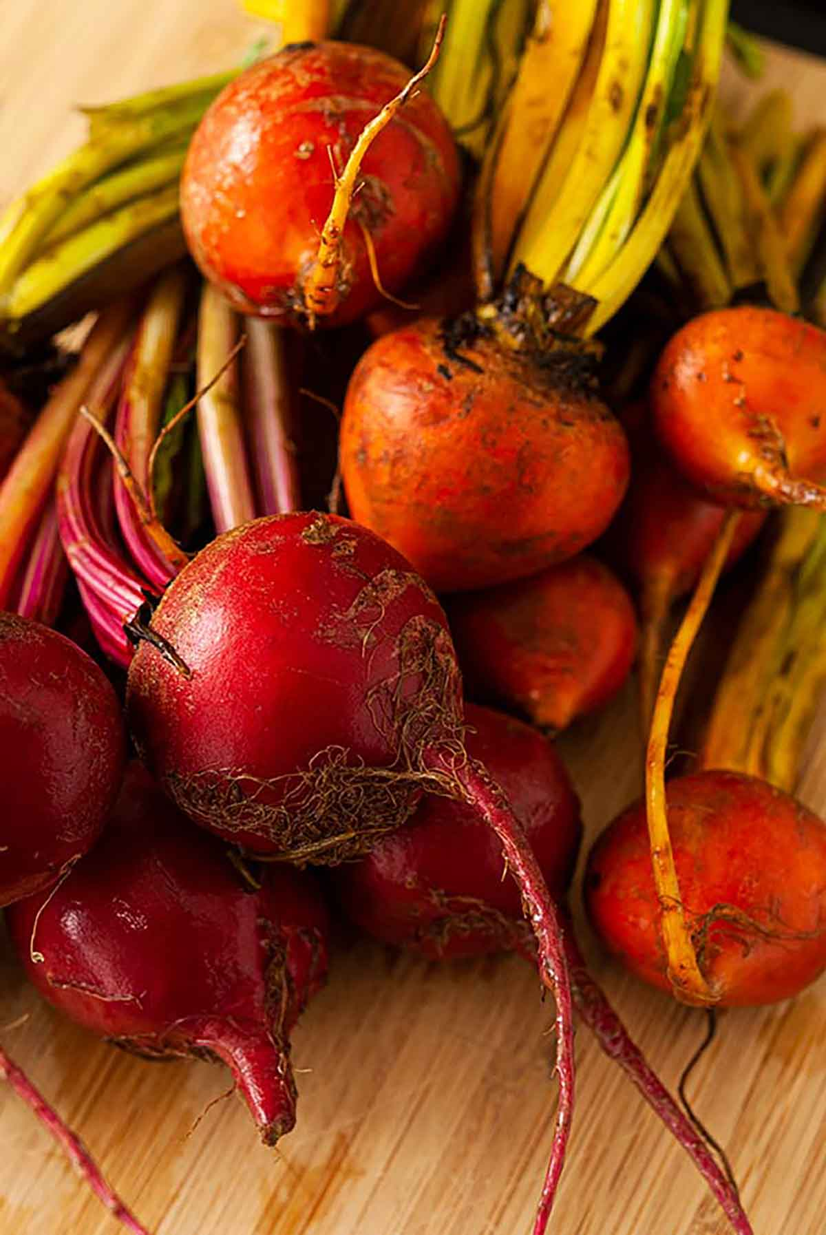 2 varieties of raw beets on a wooden cutting board.