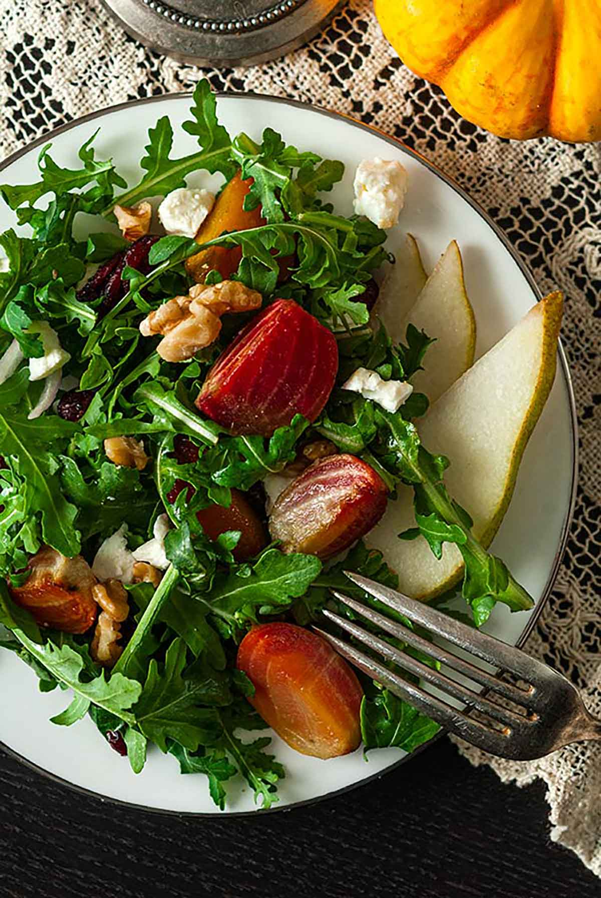 A beet and pear salad on a plate, on a lace table cloth.