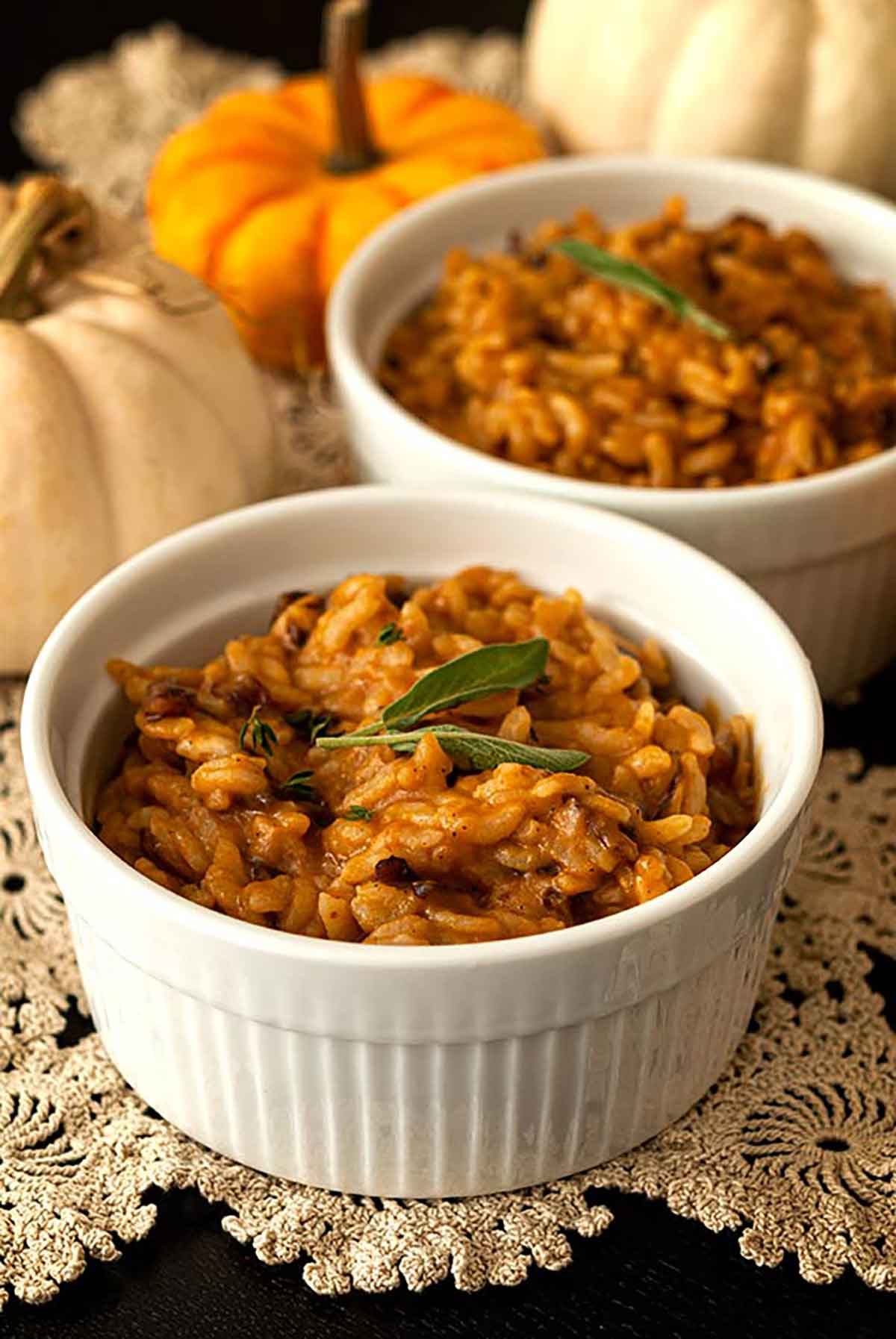 2 bowls of pumpkin risotto, garnished with sage leaves, on a lace table cloth with 3 small pumpkins in the background.