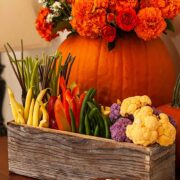 A flower box crudités on a table in front of a pumpkin full of flowers.