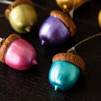 5 painted acorn ornaments on a table, in different colors.