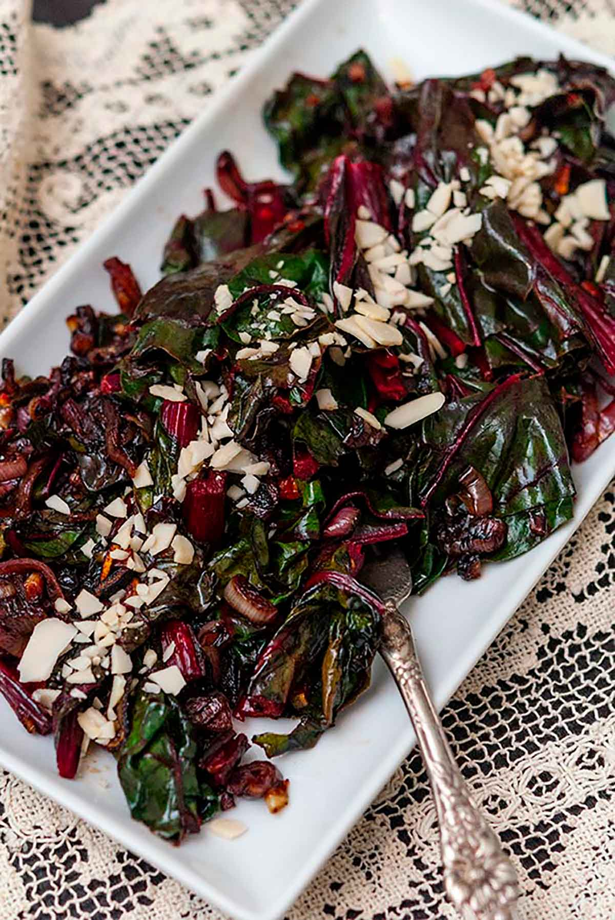 A plate of Swiss chard on a lace table cloth.