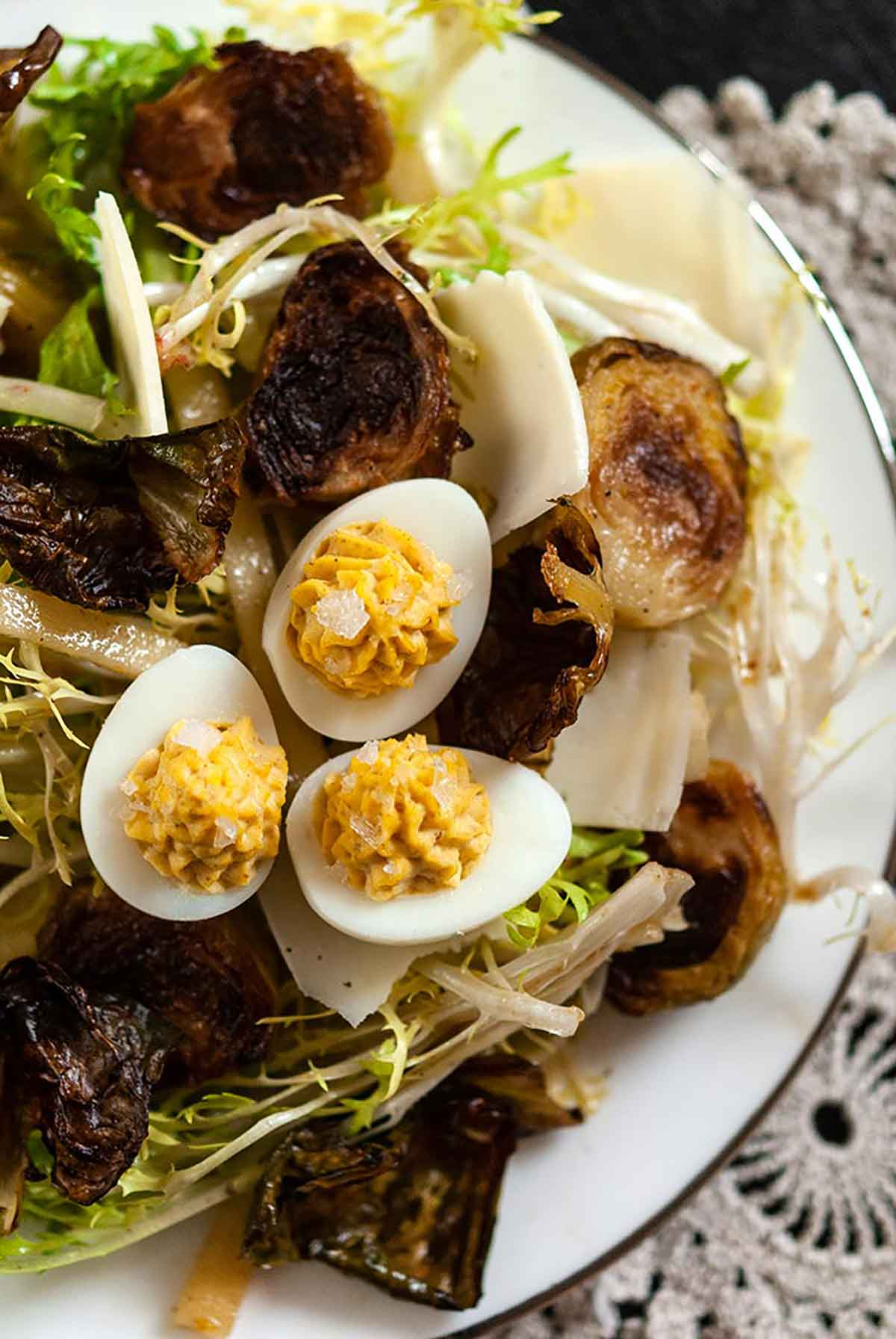 A plate of Brussels sprouts salad topped with quail deviled eggs.