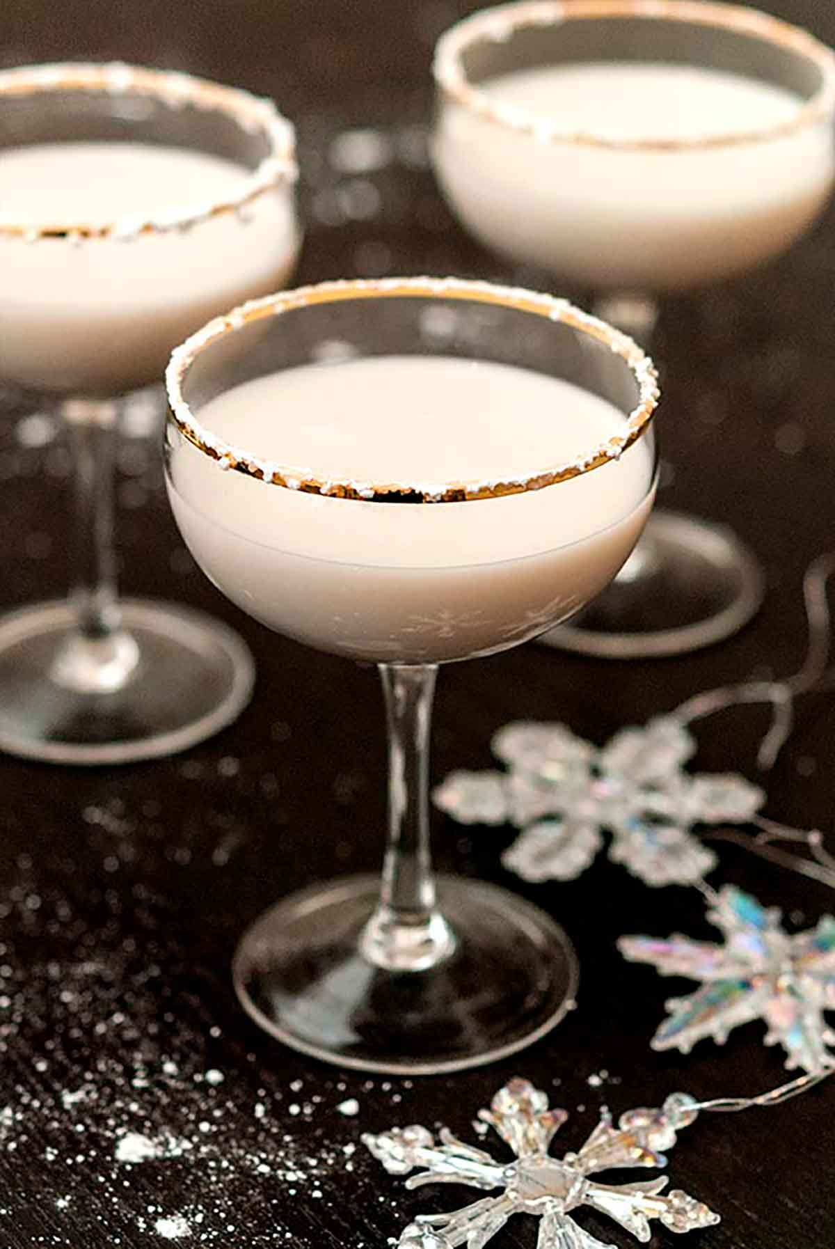 3 white cocktails, rimmed with powdered sugar, on a black table, sprinkled with sugar and with a few snowflake ornaments.