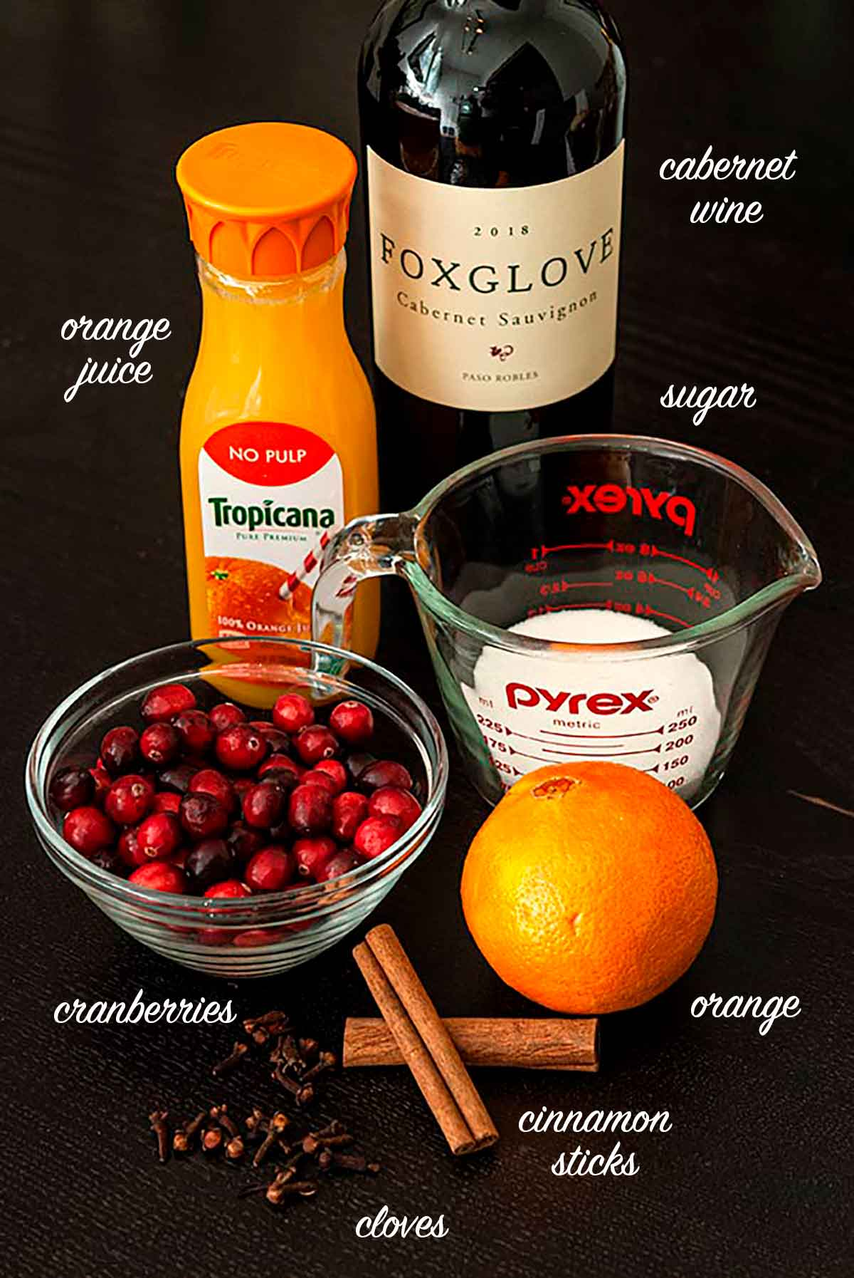 A group of ingredients for spiced Cabernet cranberry sauce on a table.