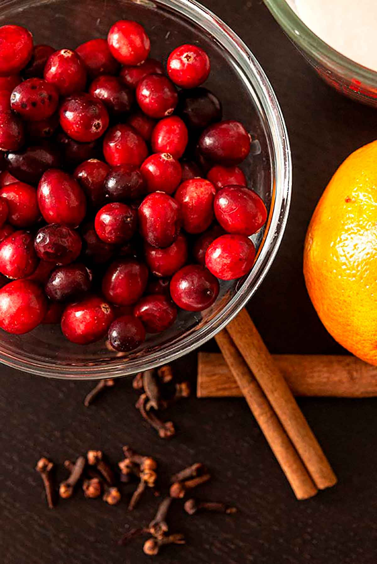 A bowl of cranberries beside 2 cinnamon sicks, a sprinkling of cloves and an orange on a table.